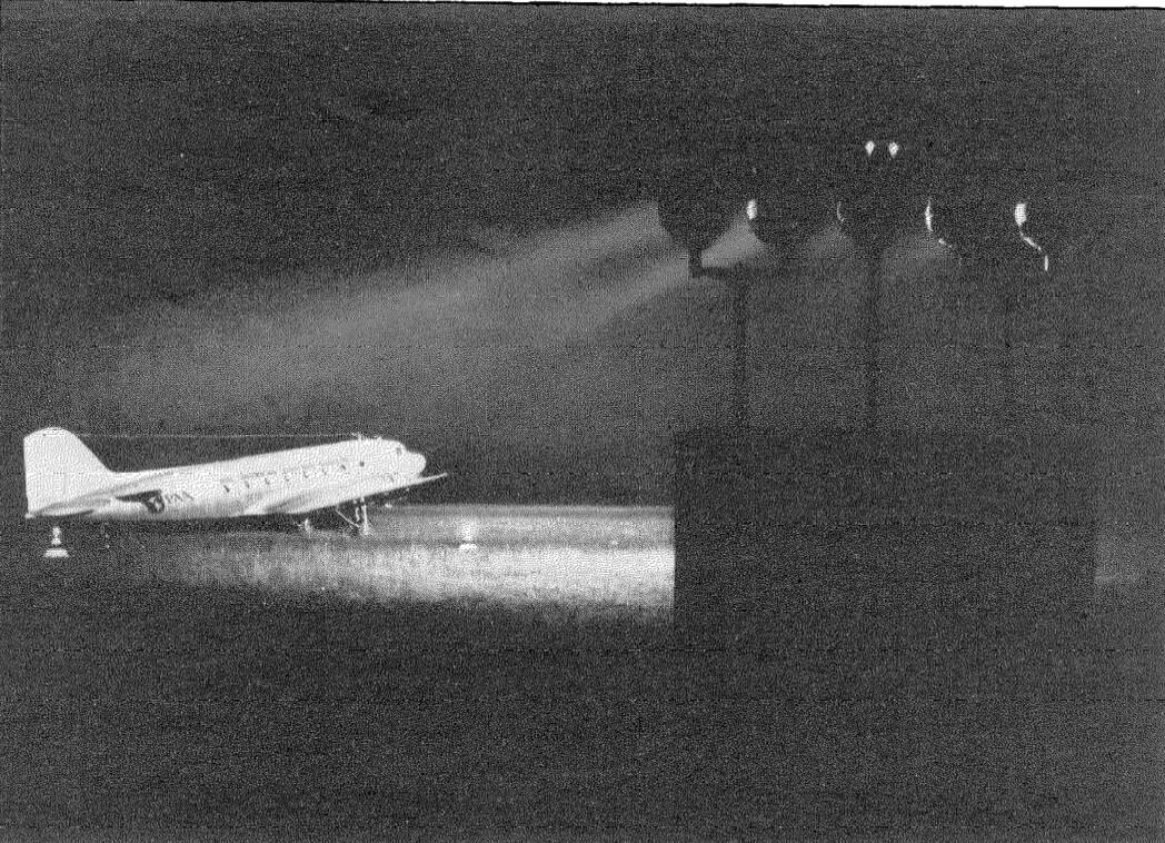 Vista nocturna de reflectores, mostrando un avión Panair a punto de despegar en Buenos Aires