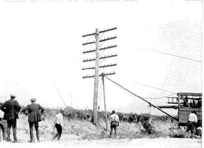 Grúa desplazando un poste telegráfico de 6 brazos